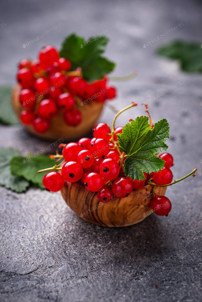 Ripe red currant berries in wooden bowls