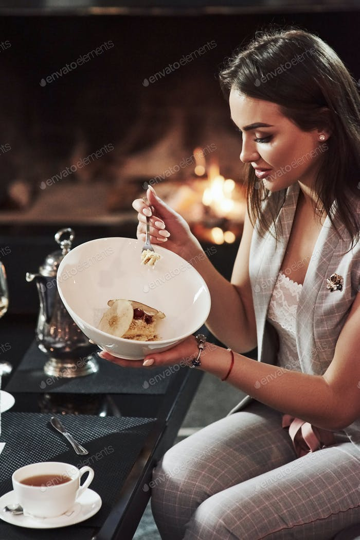 Delicious food. Cute girl with black hair trying new cake while sits against beautiful fireplace