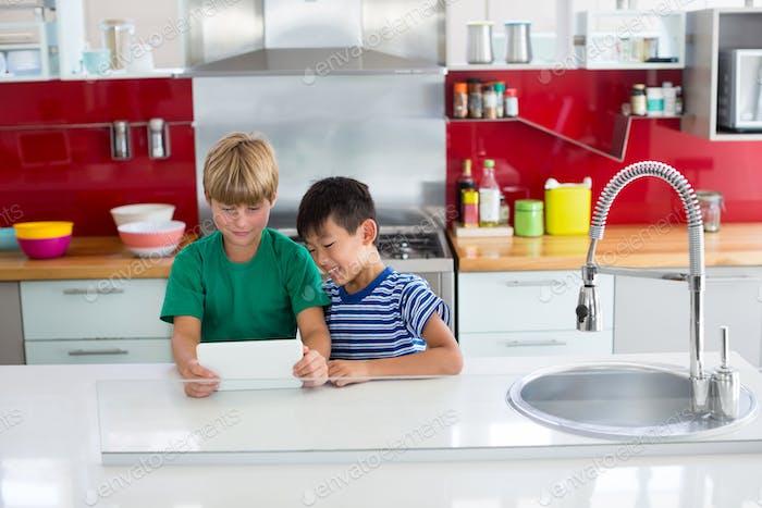 Siblings using digital tablet in kitchen