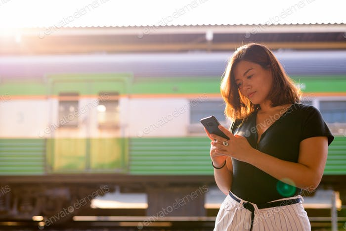 Young beautiful Asian tourist woman using phone at the railway station