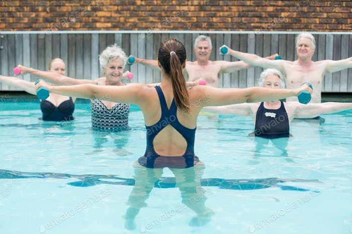 Instructor with senior swimmers exercising in swimming pool