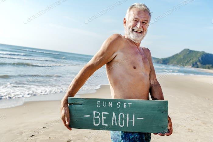 Hombre mayor sosteniendo un tablón con Sunset Playa