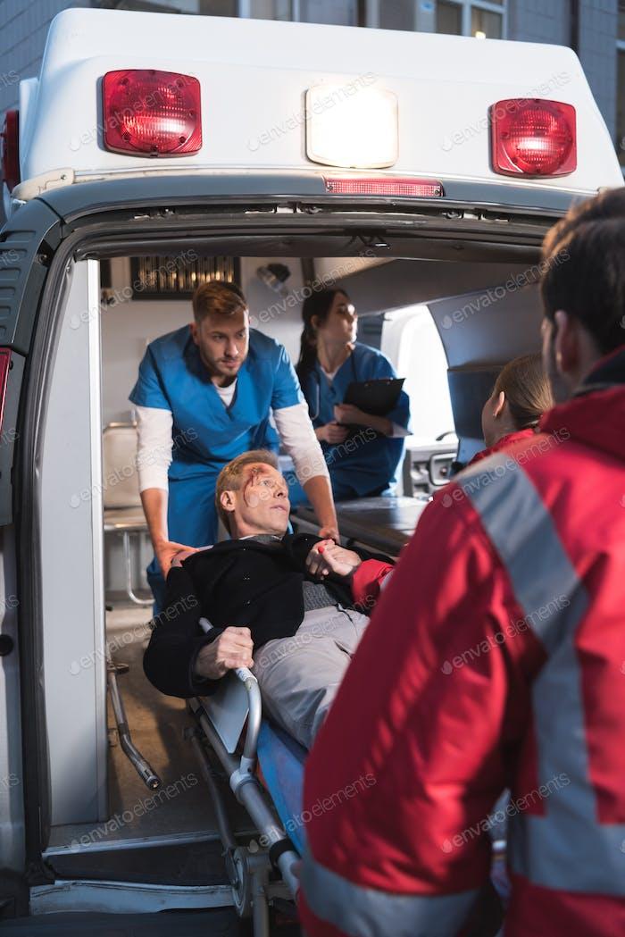 paramedics moving injured man into ambulance