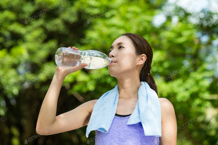 Young woman having rest after sport exercises holding bottle of water