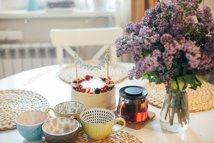 Happy Birthday at home, teatime. Birthday cake, cups, bouquet of lilacs