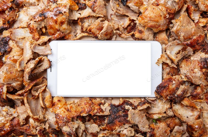 Shawarma, gyros, online order. Traditional turkish, greek meat food and a mobile phone