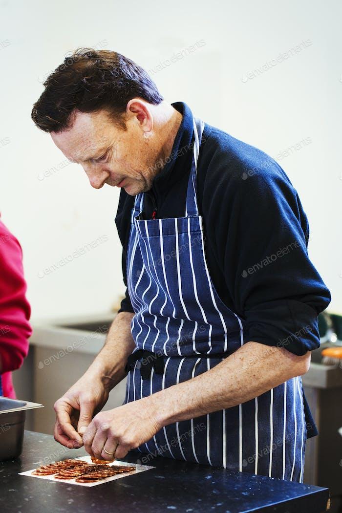 Nahaufnahme von einem Metzger trägt eine gestreifte blaue Schürze, Verpackung Scheiben von Salami.