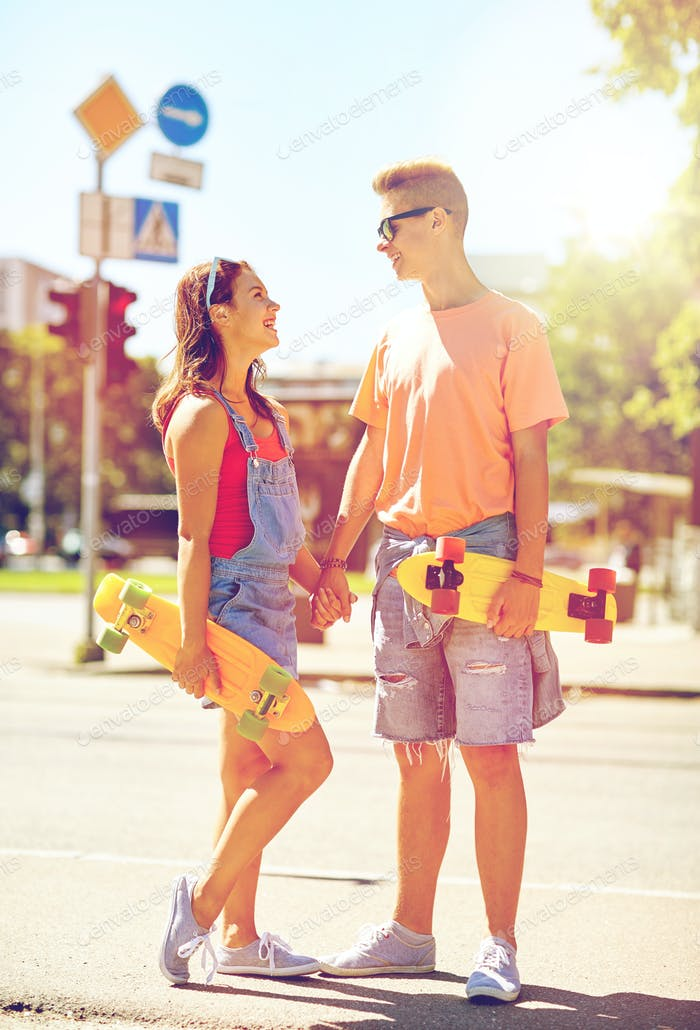 teenage couple with skateboards on city street