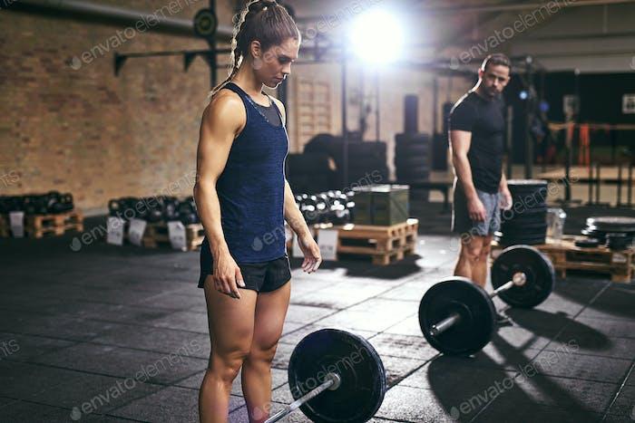 Мускулистые мужчина и женщина, стоящая в штанги