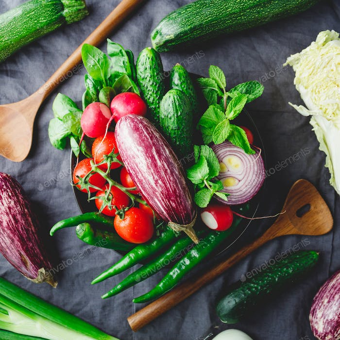 Different fresh colorful vegetables in a plate on a table, flat lay, top view.