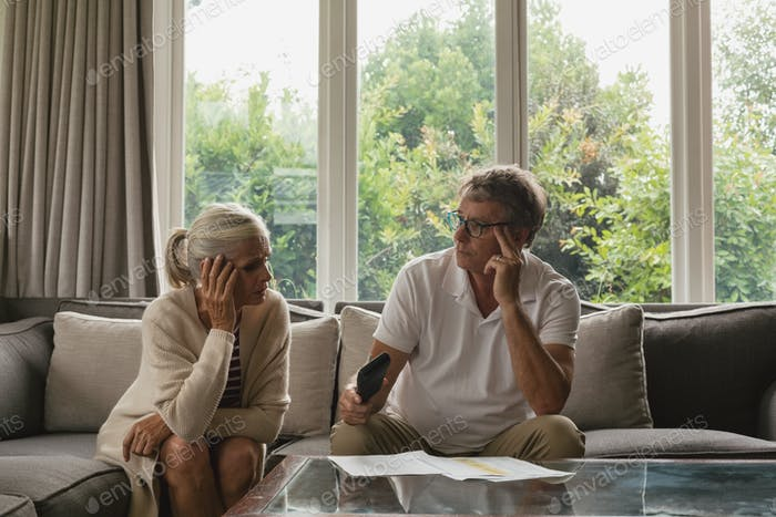 Active senior Caucasian couple calculating domestic bills on sofa in living room
