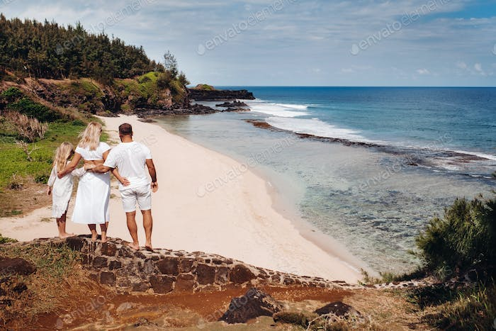 a family in white with three people looks into the distance of Gris Gris beach on the island of
