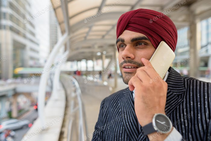 Indian businessman with turban outdoors in city talking on phone