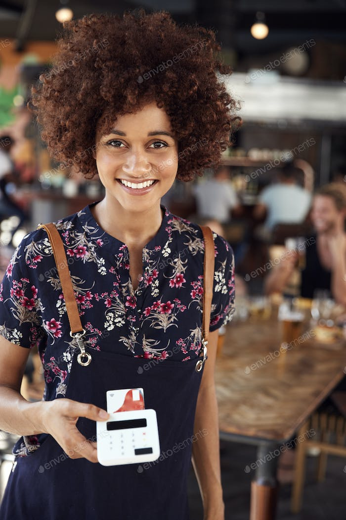 Portrait Of Waitress Holding Credit Card Payment Terminal In Busy Bar Restaurant