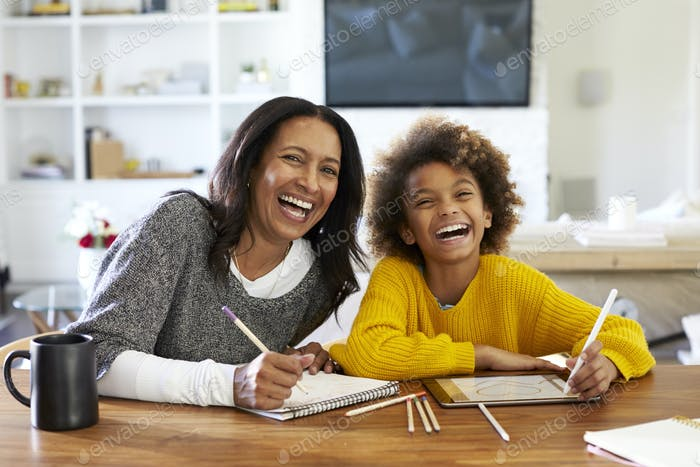 Mixed race woman sitting at table in her dining room drawing with her pre-teen granddaughter