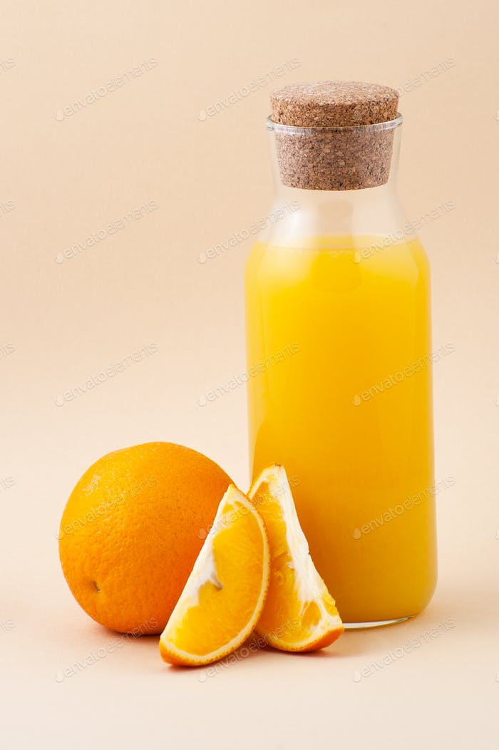 Fresh orange juice in a glass bottle and orange on a light beige