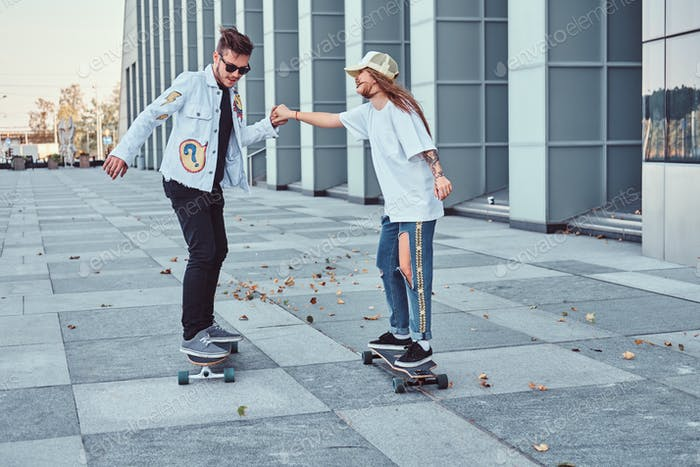 Attractive trendy dressed couple with skateboards outdoors