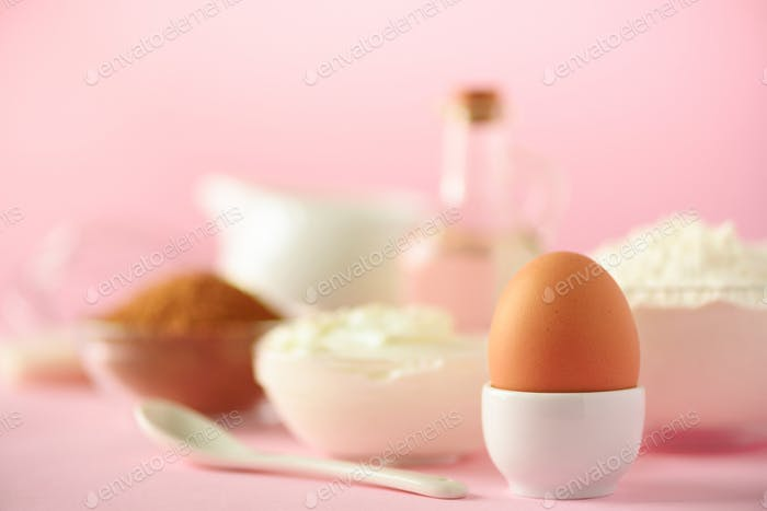 White cooking utensils on pink background. Food ingredients. Macro of egg. Cooking cakes and baking