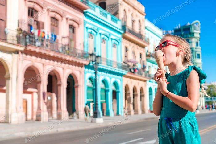 Adorable little girl eating ice-cream in popular area in Old Havana, Cuba. Portrait of cutiest kid