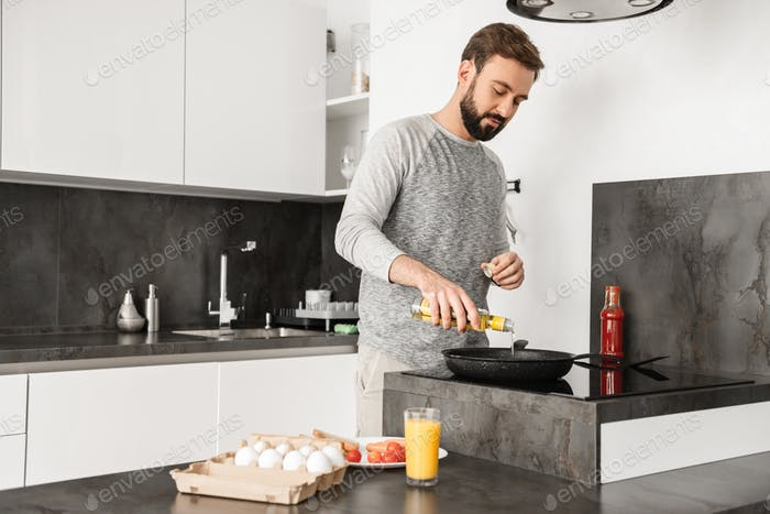 Handsome bachelor with short brown hair and beard cooking omelet
