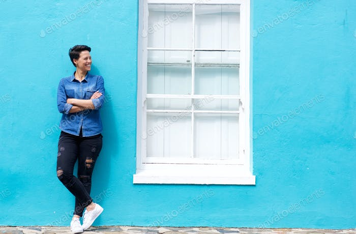 Happy young woman standing next to window