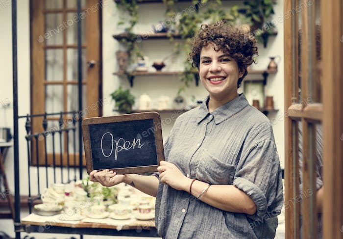 Shop owner holding an open sign
