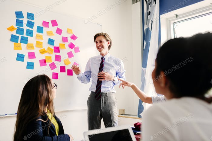 Business people with sticky notes on whiteboard