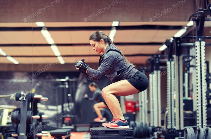 woman doing squats on platform in gym