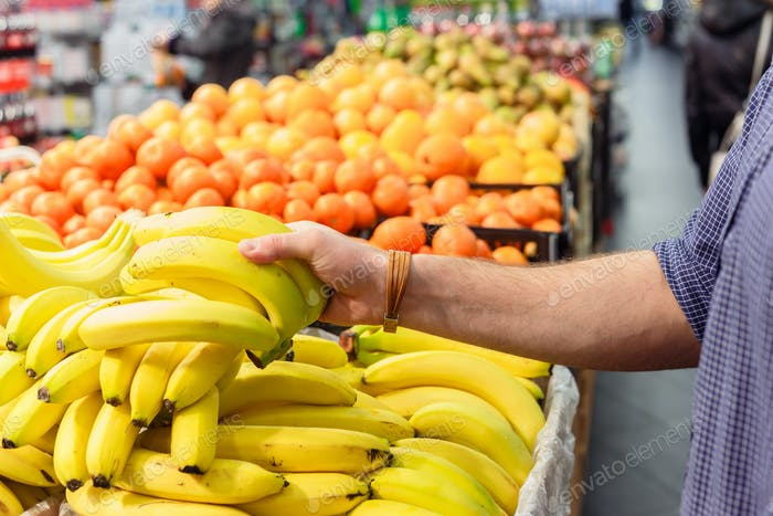 mans hand take bananas from shelf of store. healthy food. shopping concept
