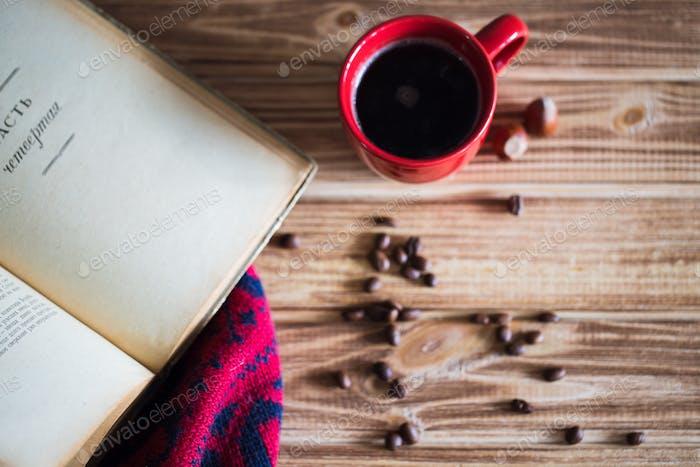 Tasse Kaffee und Bücher auf Tischdecke auf Holzhintergrund