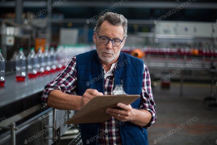 Männliche Fabrikarbeiter Aufrechterhaltung Rekord auf Zwischenablage