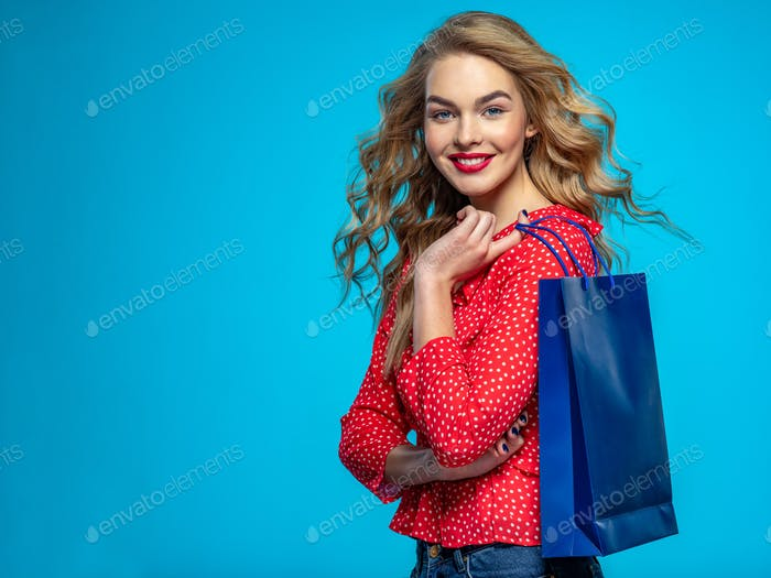 Cheerful  young woman holds bags with a purchases.