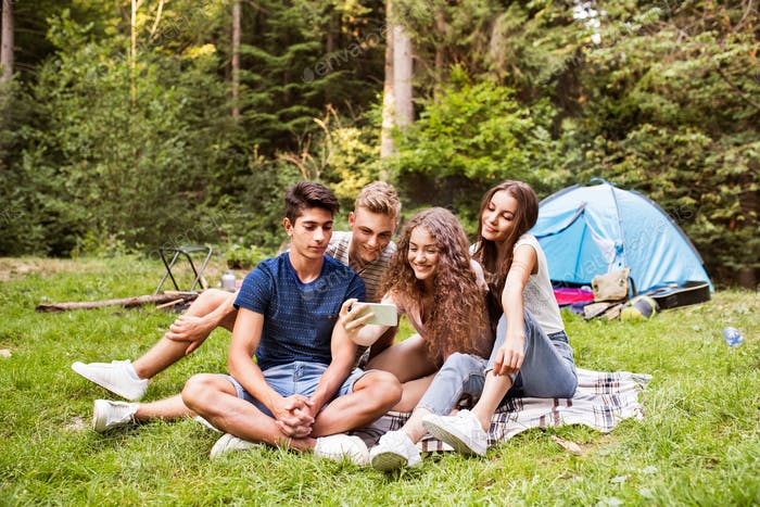 Teenagers in front of tent camping in forest.