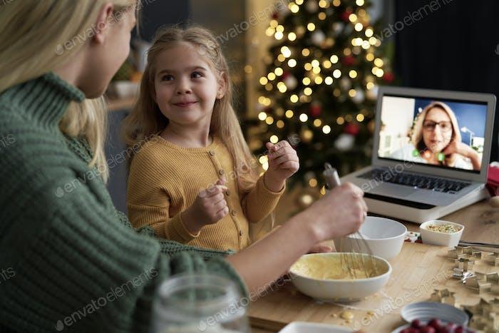 Kleines Mädchen mit lustigem Gesicht beim Weihnachtsbacken mit Familie