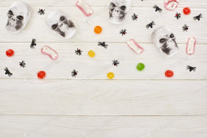Top View of Bonbons, Gummy Teeth, Skulls And Spiders on White Wooden Table, Halloween Treat