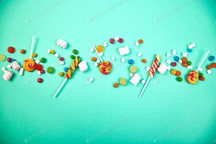 Colorful candies on pastel turquoise background. Flat lay