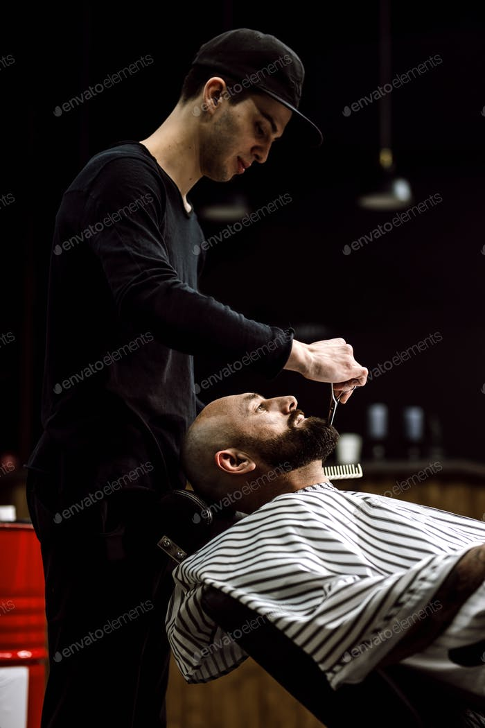 Men's fashion. The barber dressed in a black clothes scissors beard of brutal man in the stylish