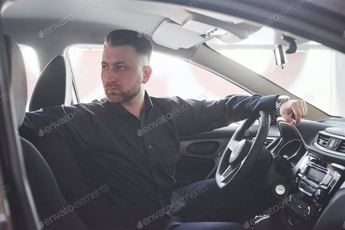 Going back. Side view of man sitting in the modern car with black interior