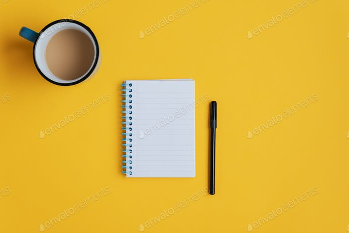 Note pad and marker on yellow background