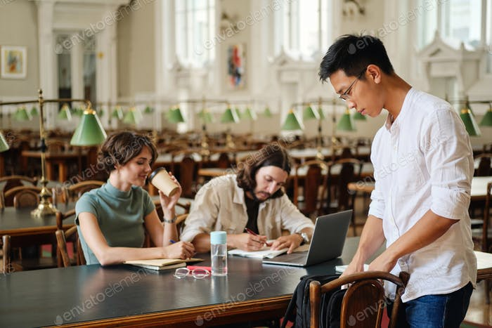 Asian male student in eyeglasses with backpack coming to study with friends in library of university