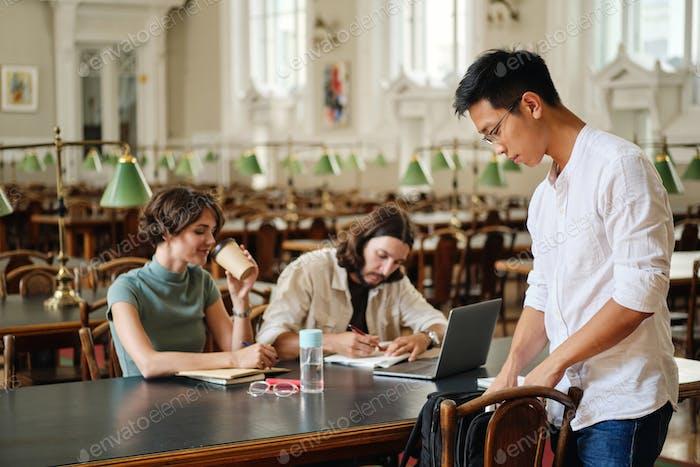 Asiatische männliche Student in Brille mit Rucksack kommen, um mit Freunden in der Bibliothek der Universität zu studieren