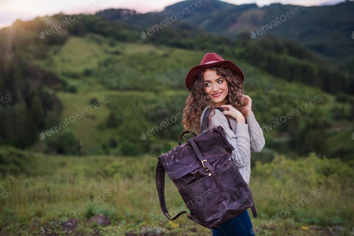 Young tourist woman traveller with backpack walking in nature