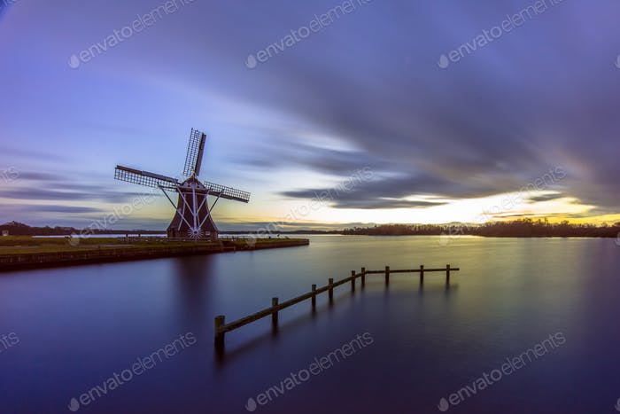 wooden windmill under long exposure sunset