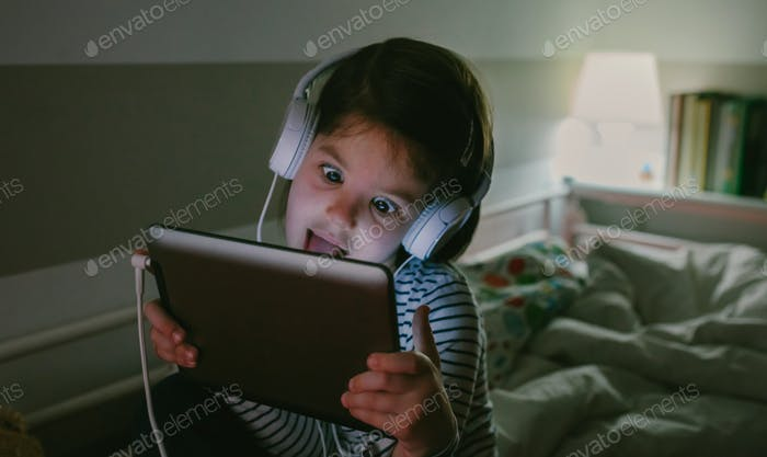 Girl grimacing with headphones looking at the tablet