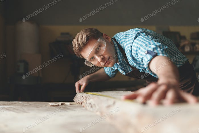 Young master with glasses in carpentry