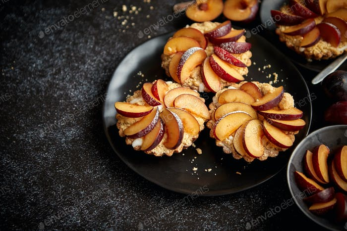 Delicious homemade mini tarts with fresh sliced plum fruit