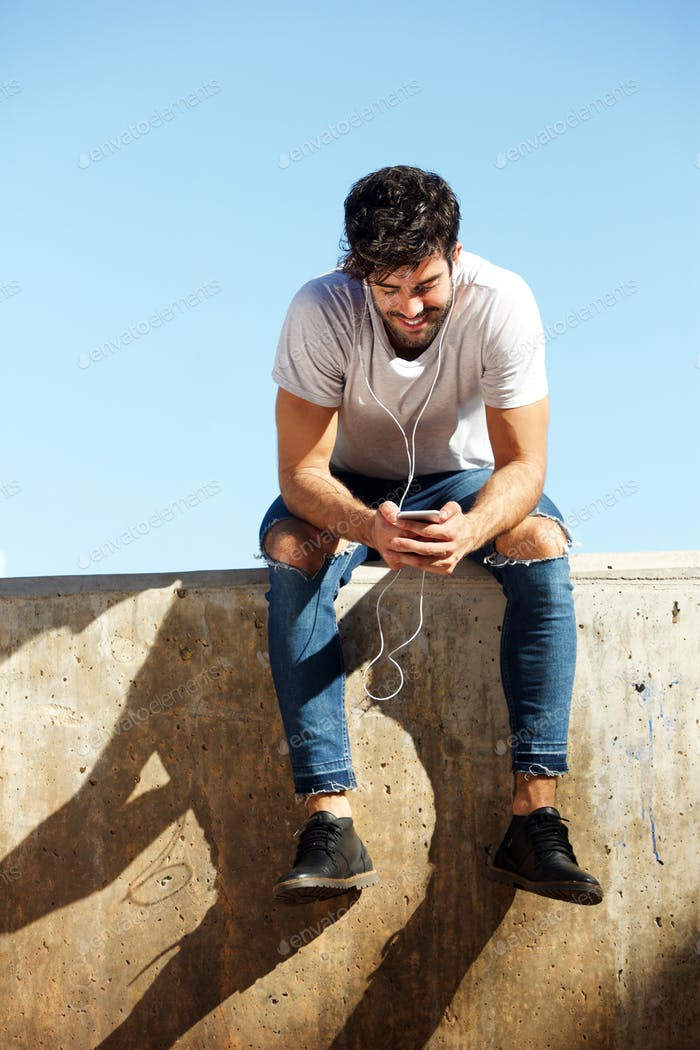 Full body cheerful man sitting on concrete wall with headphones and cellphone