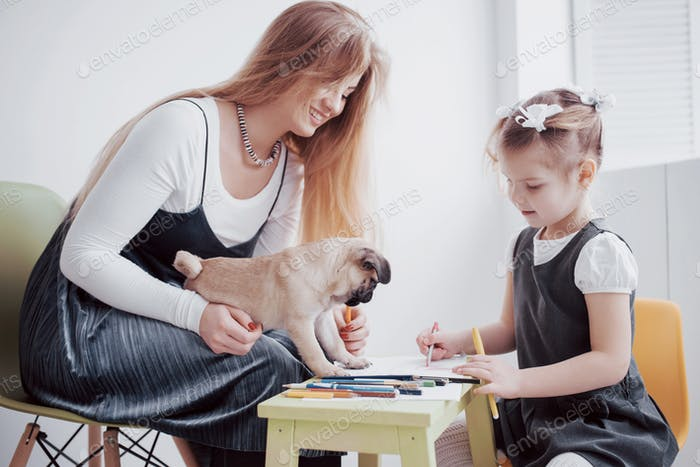 mother and child daughter draws are engaged in creativity in kindergarten. small pug with them