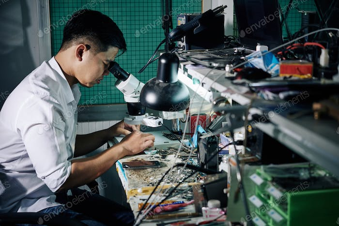 Repairman looking through microscope