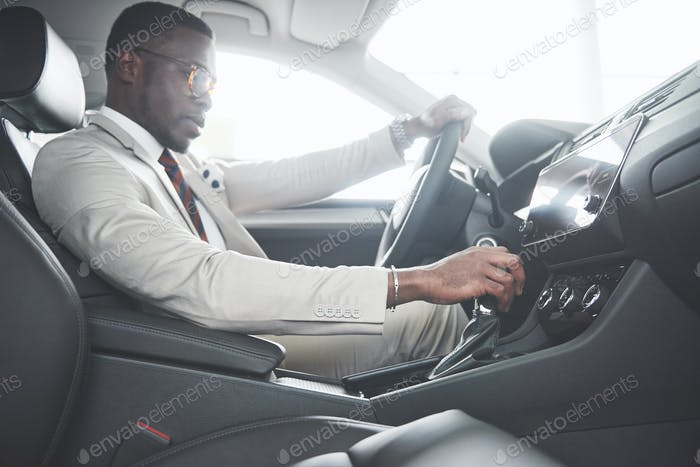 Стильный черный бизнесмен сидит за рулем нового роскошного автомобиля. Богатый афроамериканка